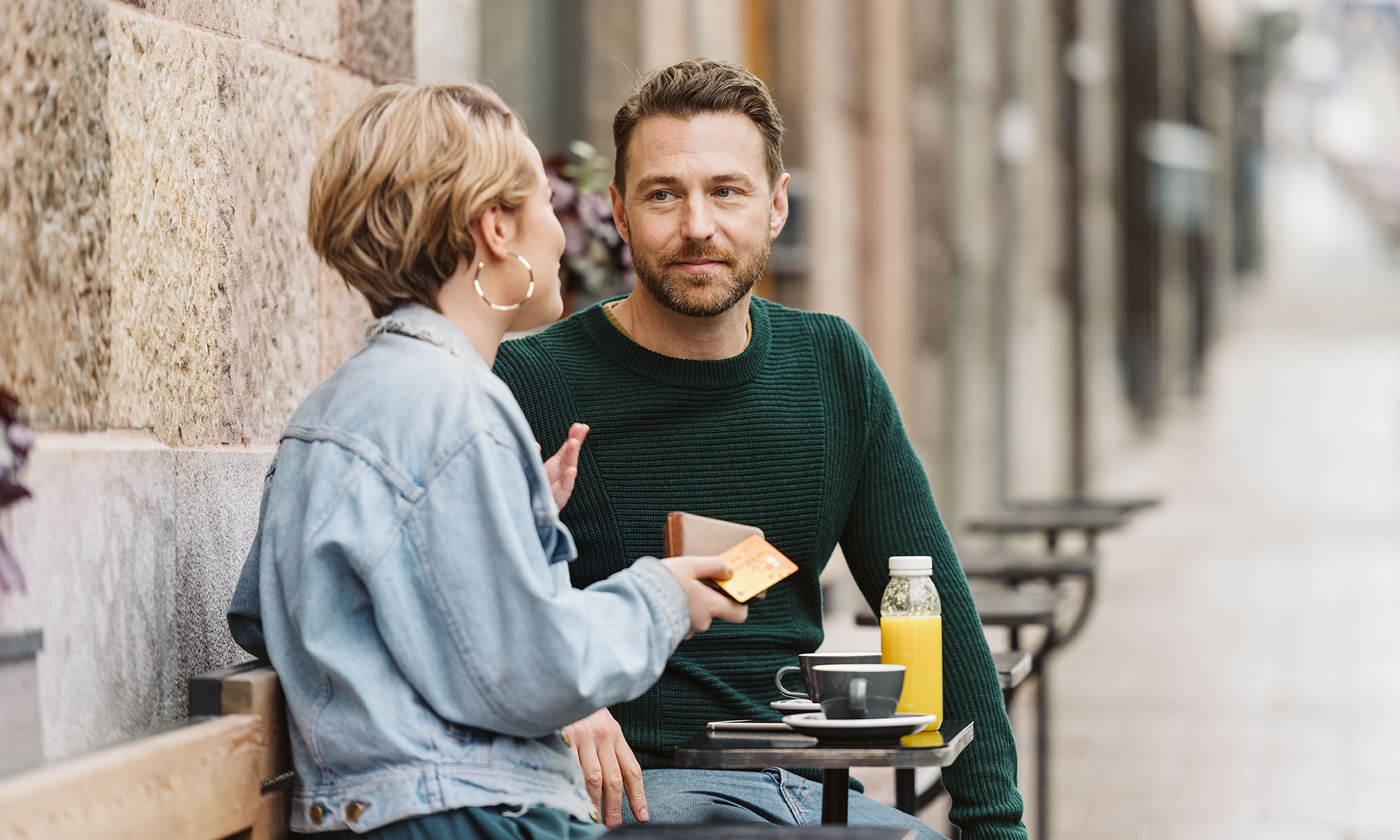 Woman and man sitting outside a café.